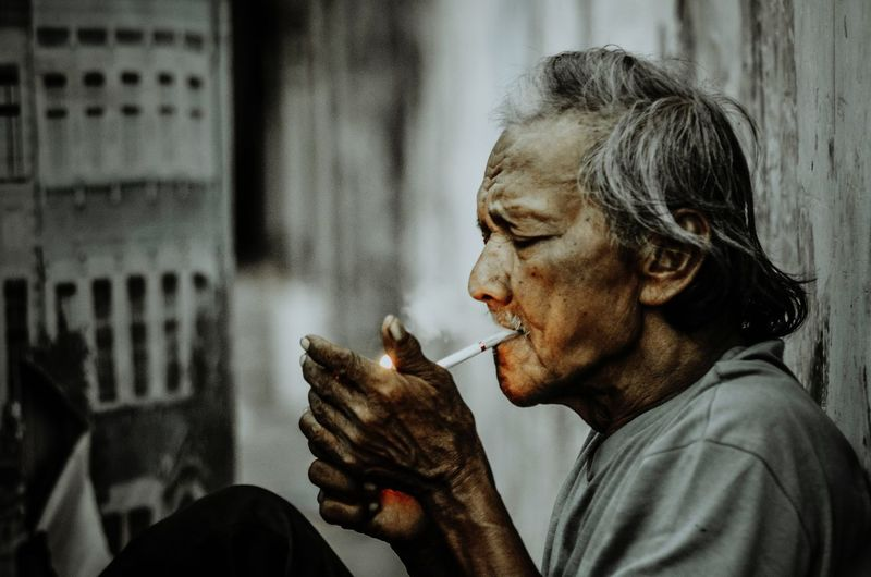 Close-up of mature man smoking cigarette by wall