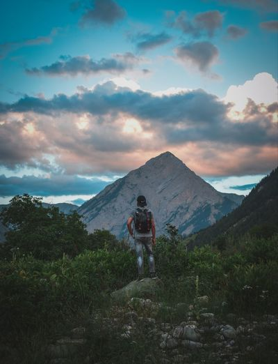 Rear view of young man standing on mountain against sky during sunset