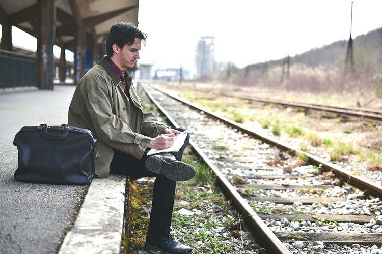 Man sitting at railroad station during winter