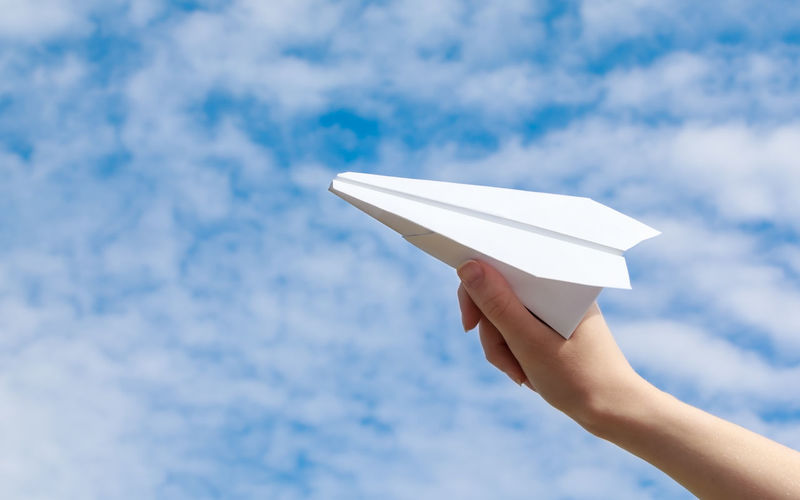 Cropped hand of woman playing with paper airplane against cloudy sky