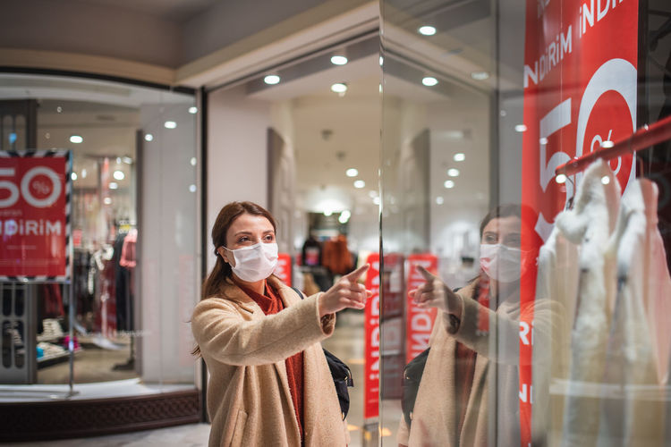 Happy woman wearing mask pointing at garment in store