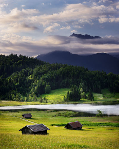 Geroldsee view during summer day with foggy sunrise. Rainy cloudy sky and huts in mountains near beautiful lake. Bavarian Alps, Bavaria, Germany. Bavaria Alps Beauty In Nature Cloud - Sky Day Environment Field Garmisch-partenkirchen Germany Grass Green Color Growth Land Landscape Mountain Nature No People Non-urban Scene Outdoors Plant Scenics - Nature Sky Tranquil Scene Tranquility Tree