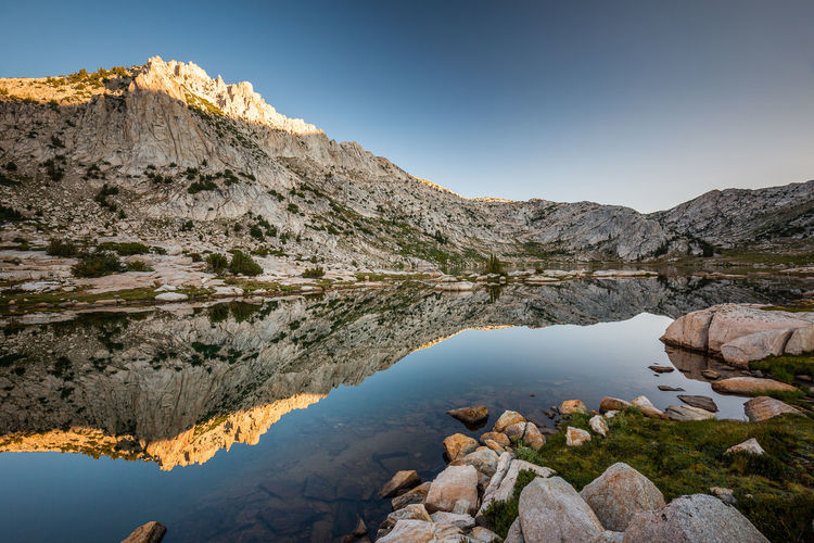 Simply pleasing to eye | JMT DAY 10 - SUNRISE AT SILVER PASS LAKE Sunrise at Silver Pass Lake When I peeked out of my tent, it was still dark and definitely chilly. I knew that daybreak was still a half hour away but that it was time to get moving. I grabbed my gear and hurriedly headed over the huge rock near the outlet of the lake. I had already climbed to the top and scouted the area the day before, so I knew that I would have a great view of the layers of mountains in the east. From Mt. Gabb (13,741') on the left to Mt. Hilgard (13,361') all the way to Mt. Hooper (12,349') on the right. Once it was done, I quickly returned to the lake and set up my camera to capture the glow on the ridge in the west side of the lake. To my pleasant surprise, the calm water reflected the rocky ridgeline that ran all the way to Silver Pass like mirror. It was simply pleasing to the eye. I wished I had had more time to stick around and enjoy the morning, but it was time to pack up and get on with the day. We had a bit of distance to cover (just over 7 miles) to reach the east end of Thomas Edison Lake to catch a ferry. Our destination - VVR. Silver Pass Lake, Sierra National Forest, CA Water Beauty In Nature Rock Scenics - Nature Tranquility Tranquil Scene Mountain Sky Rock - Object Nature Non-urban Scene Mountain Range Lake Idyllic Clear Sky Outdoors Mountain Peak Silver Pass Lake, Sierra Nevada Silver Pass, Sierra Nevada Sunrise Sunrise Glow Reflection Sierra Nevada Eastern Sierra Wilderness