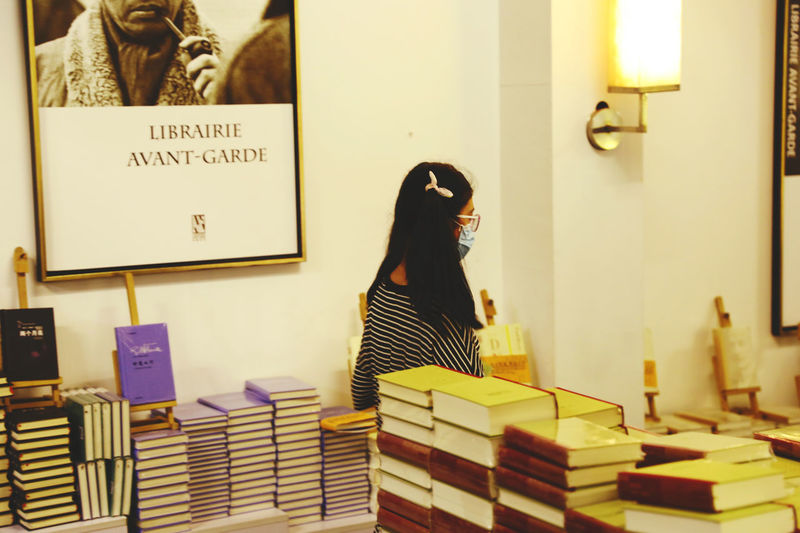Woman standing on book at store