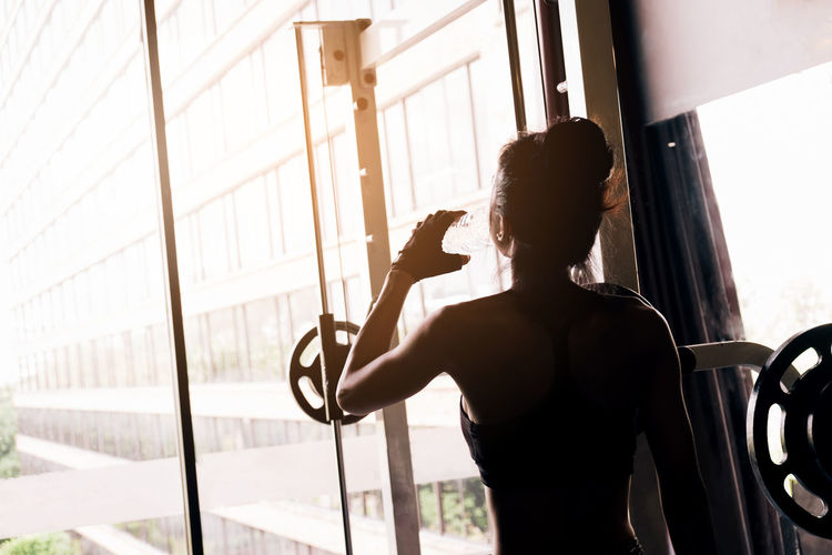 Rear view of woman drinking water while standing by window at gym