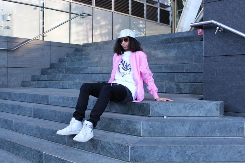 Steps And Staircases Staircase Long Hair Fashion Adults Only Adult People Young Adult City Lifestyles Sitting Day Outdoors Steps Only Men Pink Color Confidence  Cool Attitude Fashion Human Body Part One Man Only Confidence
