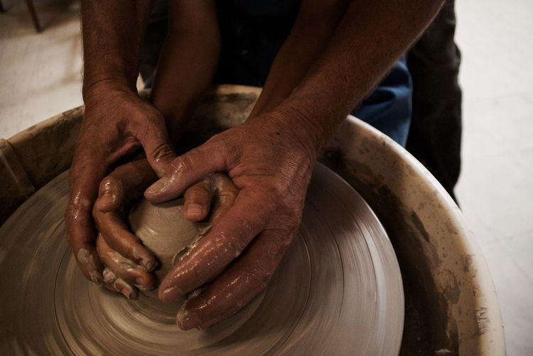 Cropped Hands Of Man Assisting Child While Making Pot In Workshop