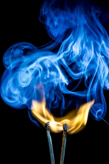 Close-up of burning matchstick with smoke against black background