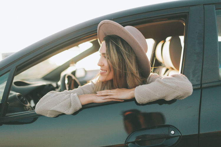 Smiling woman looking through window while sitting in car