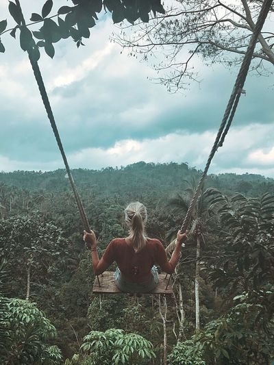 Rear view of woman swinging over trees against cloudy sky in forest
