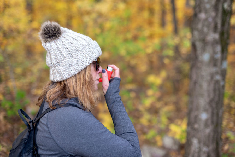 woman hiking outside in Autumn using prescription inhaler to control asthma Tree One Person Headshot Autumn Forest Women Focus On Foreground Nature Portrait Warm Clothing Outdoors Inhaler Respiratory Allergies Breath Prescription  Medicine Management Asthma Container Hiking Pulmonary Inhaling Mouth Holding