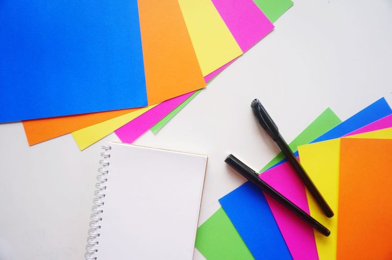 Directly above shot of multi colored papers with pens and book on gray background