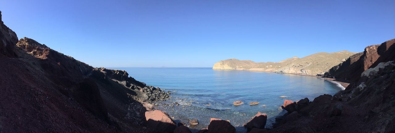 PANORAMIC SHOT OF ROCKY BEACH AGAINST CLEAR BLUE SKY
