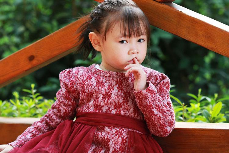 Portrait of cute girl against railing