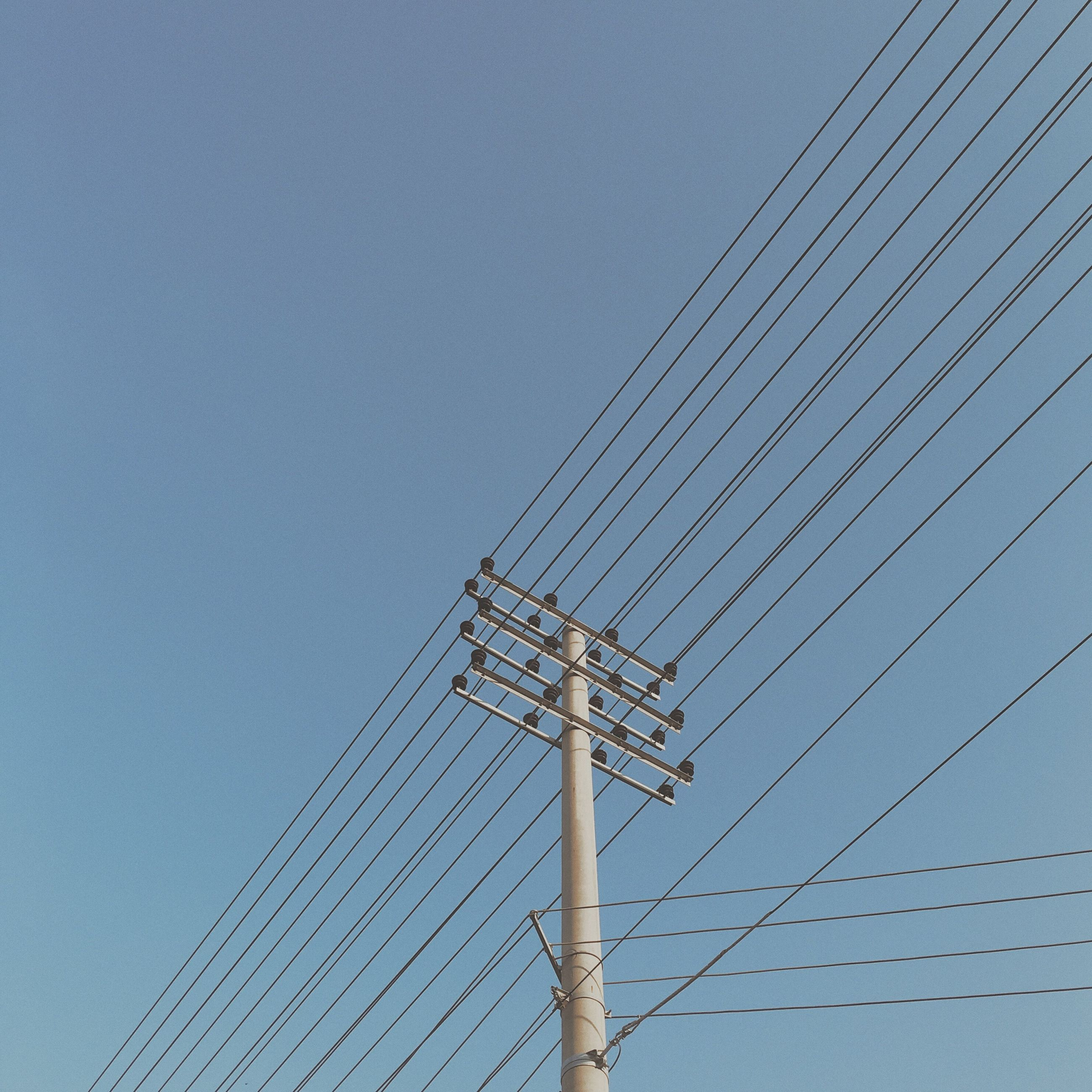 low angle view, built structure, blue, tall - high, sky, development, day, outdoors, no people, power supply, construction, tall, high section, cable, modern, pole