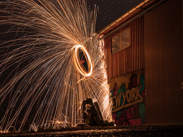 Motion Long Exposure Night Illuminated Blurred Motion Spinning Wire Wool One Person Glowing Sparks Burning Arts Culture And Entertainment Celebration Lifestyles Fire Real People Warning Sign Men Standing Sign Firework Skill  Outdoors Firework Display Firework - Man Made Object