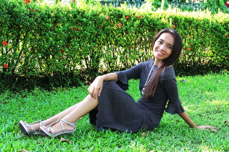 Full length portrait of smiling young woman relaxing on grassy field