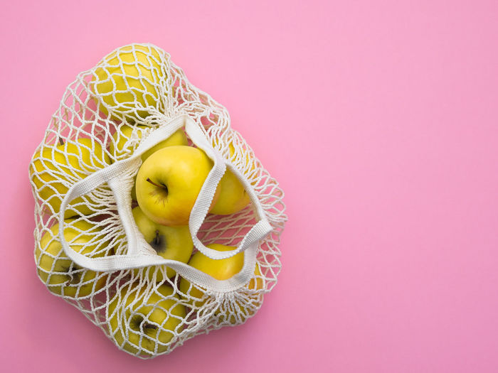 Directly above shot of lemon slice against pink background