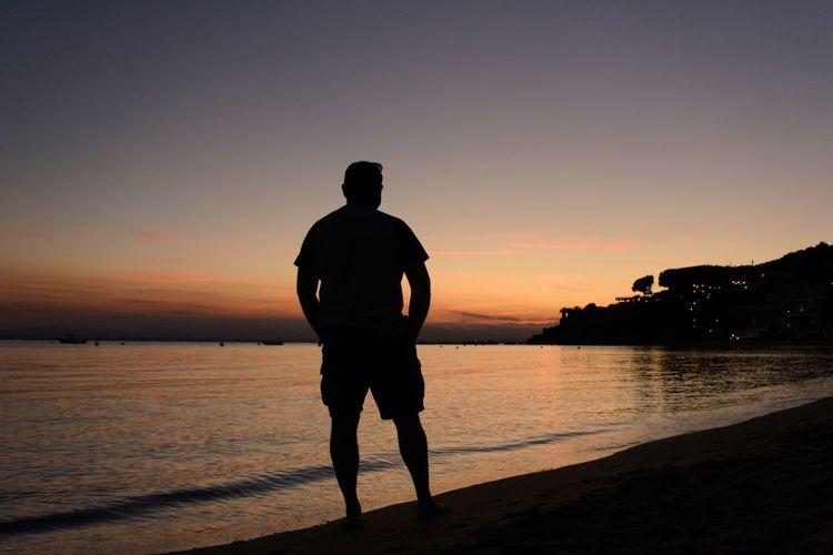 Rear view of silhouette man standing on beach against sky during sunset
