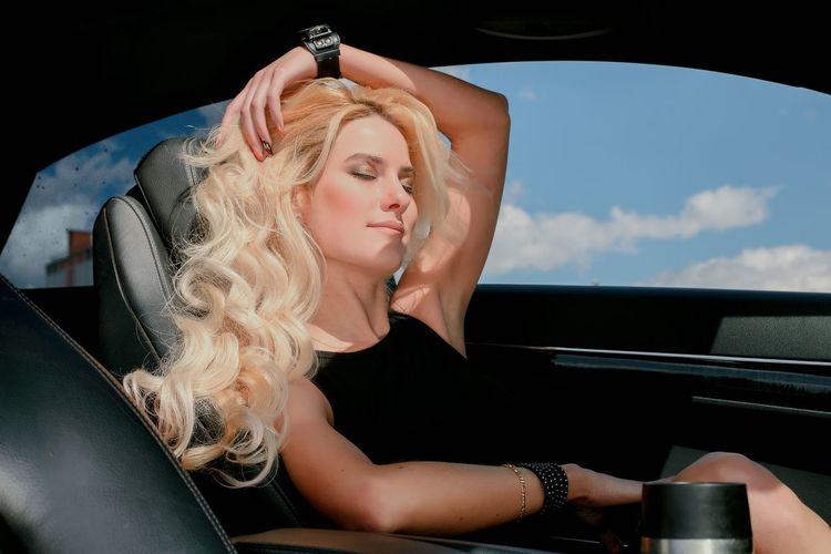 Woman with blond hair sitting in car