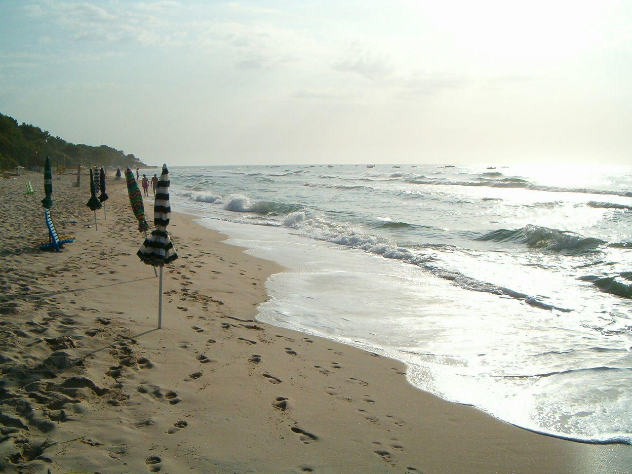 Closed Umbrella On Sandy Beach Against Sky