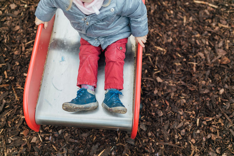 Low Section Of Child Sitting On Slide At Playground
