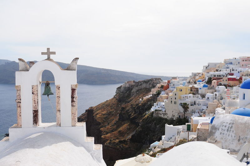 Bell tower by village at santorini against clear sky