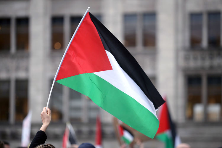 Cropped image of hand holding flag in city