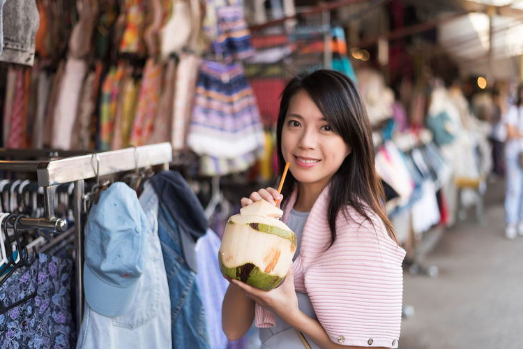Portrait of woman holding coconut at market