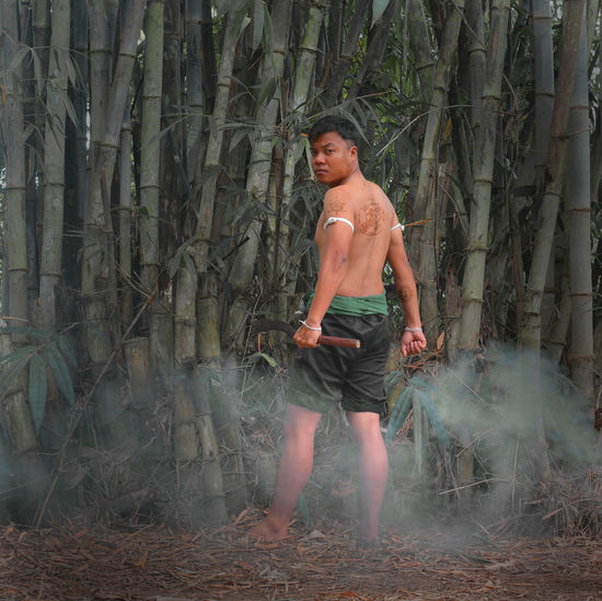 Portrait of shirtless young man standing by bamboo grooves in forest
