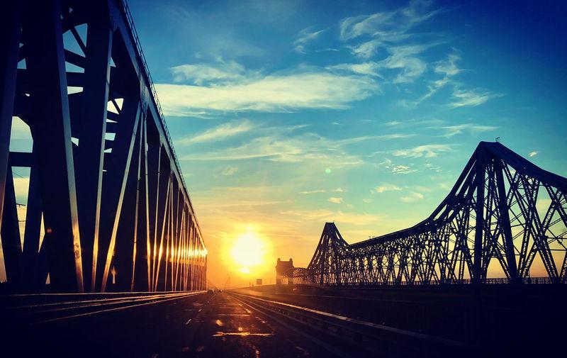 Silhouette of bridge against cloudy sky