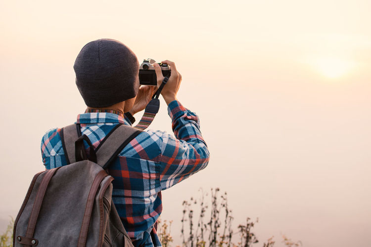 Rear view of backpacker photographing with camera against sky