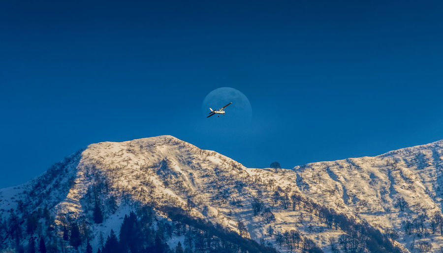 Low angle view of helicopter flying over snowcapped mountains against clear blue sky