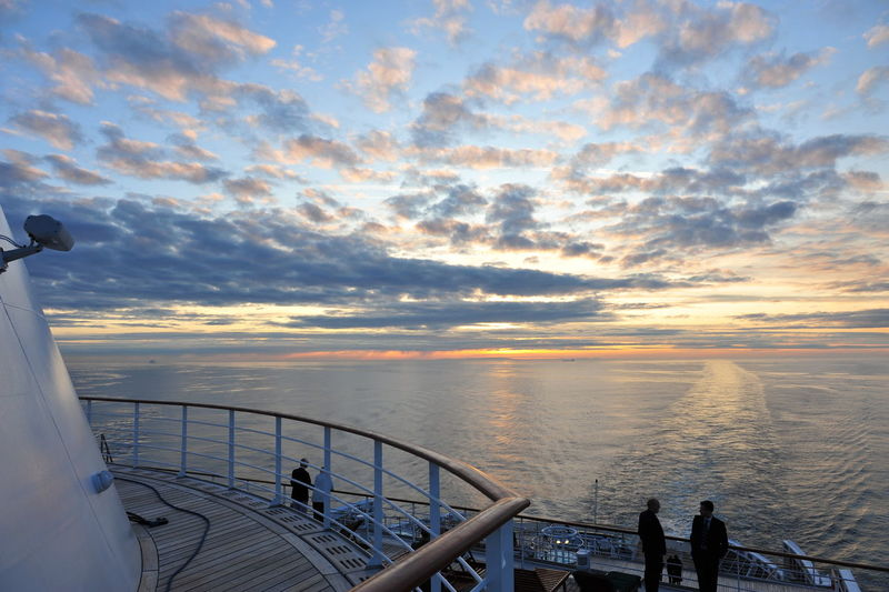 People Standing In Cruise Ship On Sea During Sunset