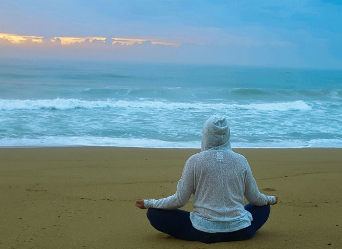 Meditating on the beach. Sunset Seaside Adult Sunrise Dawn Shore Horizon Over Water Ocean Sky Day People One Person Outdoors Wave Seascape Sand Water Sea Wave Beach Sitting Horizon Blue Summer Sand Rear View Meditating Zen-like Tranquil Scene Coast