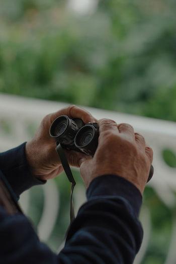 Hands of a man holding binoculars. close-up image.