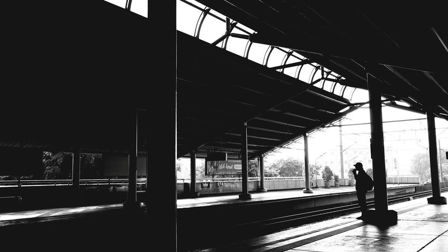 Silhouette person walking on railroad station platform