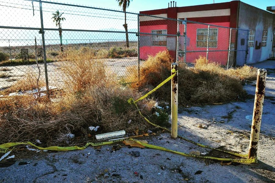 First Eyeem Photo Abandoned Color Pink Abandoned Buildings Derelict Dirty Trash Pollution Desert Broken Glass Colorful Pink Yellow Pavement Broken Salton Sea Chainlink Fence Metal Dead Plant Dry Bush Palm Trees Boarded Windows Caution Tape Crime Scene