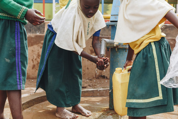 Africa African Barefoot Charity And Relief Work Child Children Day Dirty Girls Hands Midsection Muslim Outdoors PLASTIC CONTAINER Pump School Students Uniform Unsafe Washing Water Water Pump Well
