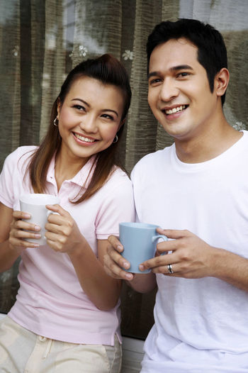 Smiling couple having coffee against wall
