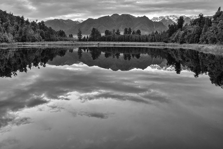 Early in the morning, the water of Lake Matheson is like a mirror. Hard to tell which is the original orientation if you flip the image. New Zealand Scenery Beauty In Nature Bnw_collection Bnw_friday_eyeemchallenge Bnw_water_reflections Cloud - Sky Lake Mirror Lake Nature New Zealand Outdoors Reflection Reflection Lake Scenics - Nature Sky Standing Water Symmetry Tranquil Scene Tranquility Water
