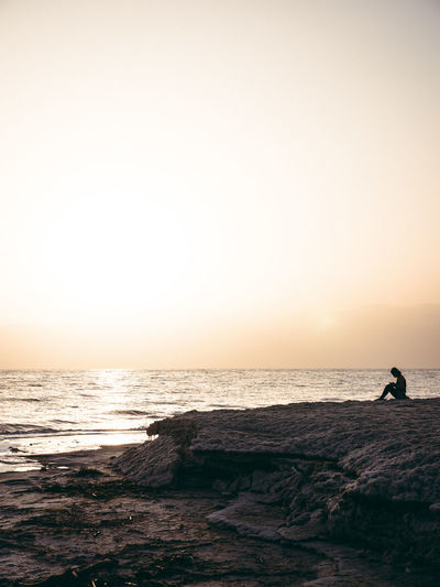 Silhouette Woman Sitting On Rocks By Sea Against Clear Sky