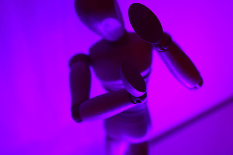 High Angle View Of Wooden Figurine Against Purple Wall