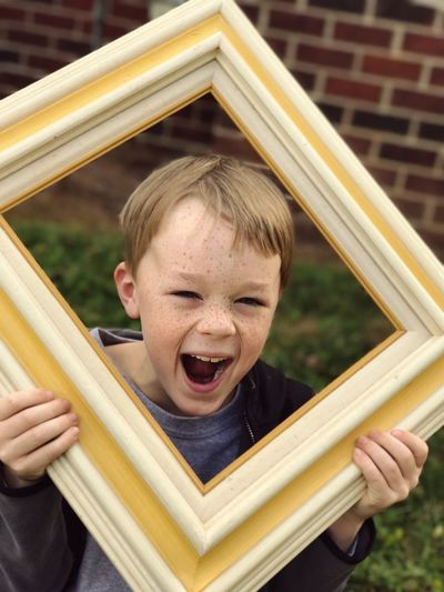 He's been framed Childhood Mouth Open One Person Child Real People Outdoors Front View Boys Fun Day Headshot Leisure Activity Portrait Playing Building Exterior Human Body Part Blond Hair Architecture Close-up People Freckles Yellow Frame Young Boy Boy With Freckles