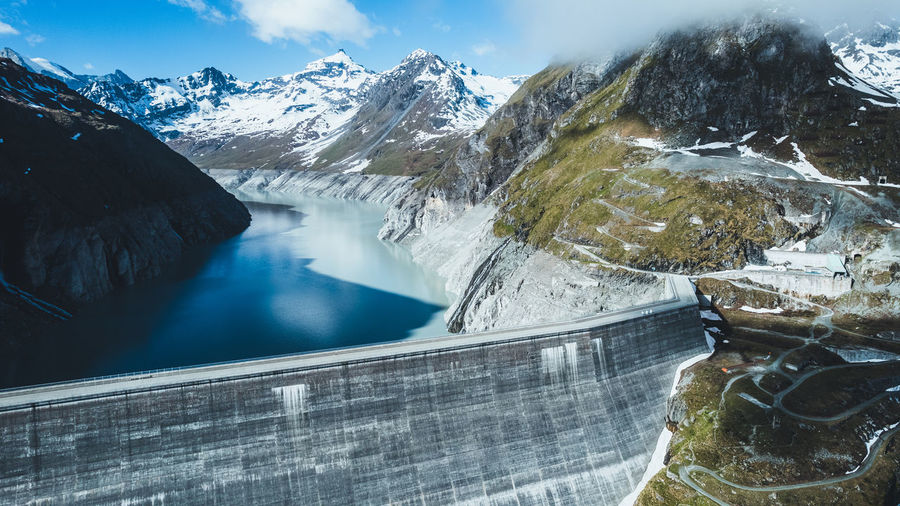 Scenic view of snow covered mountains against sky with a dam