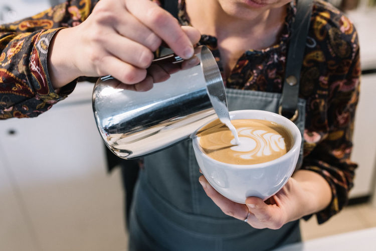 Midsection of woman pouring coffee in cup