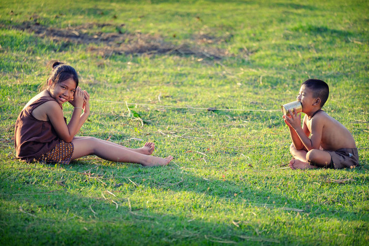 Siblings Playing On Field
