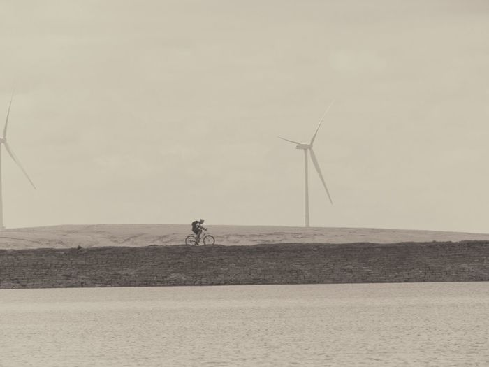 Mid distance shot of wind turbines in sea against clear sky