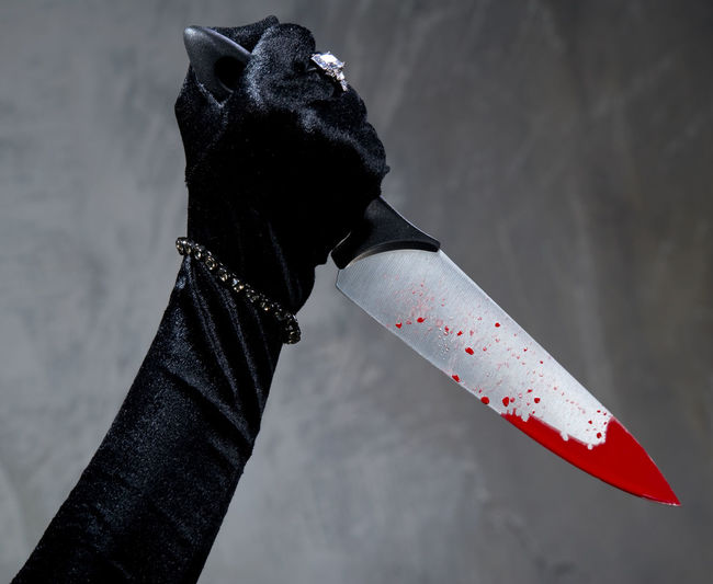 Cropped hand of woman holding blooded knife