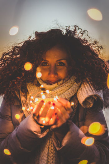 Portrait Of Young Woman Holding Illuminated String Lights In Jar